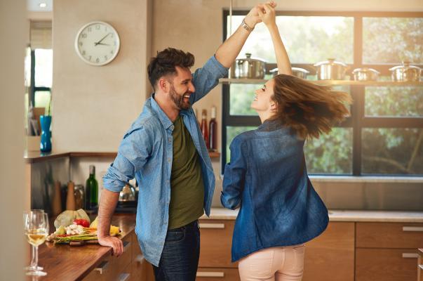 Paar tanzt zuhause Discofox. Die Dame dreht sich.