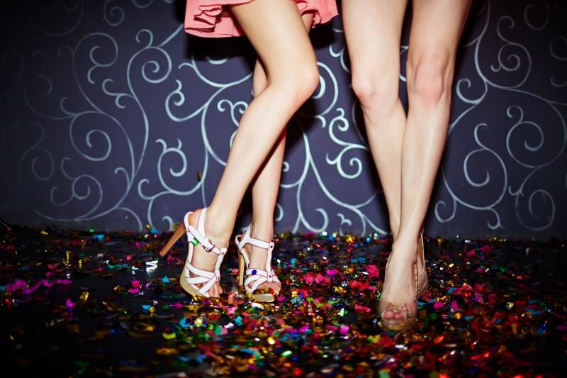 Die Beine von zwei schönen Frauen neben einer Tanzfläche