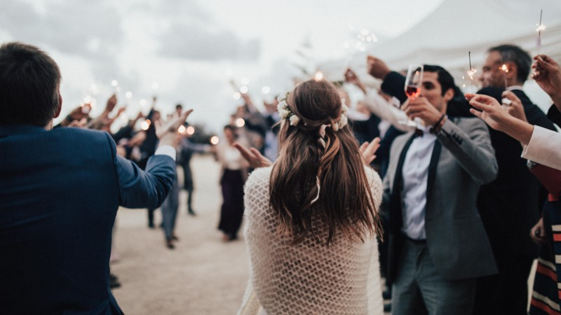 Hochzeitsgäste mit Wunderkerzen stehen im Kreis um tanzendes Brautpaar herum