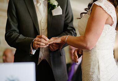 Bräutigam steckt seiner Braut den Ehering auf