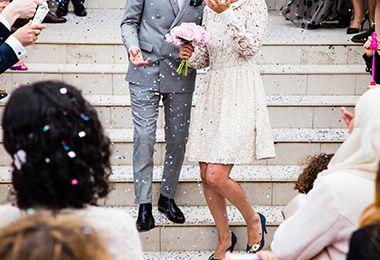 Braut und Bräutigam gehen die Stufen der Kirche herunter nach Hochzeit