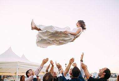 Braut wird von Hochzeitsgästen in die Luft geworfen