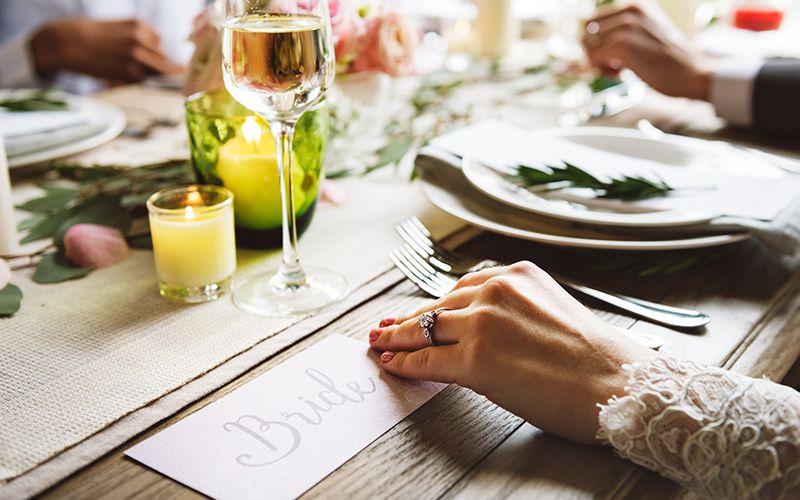 Hände von Braut und Bräutigam bei Hochzeitsessen