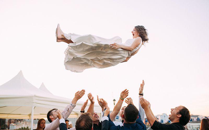 Braut wird von Gästen hoch in die Luft geworfen