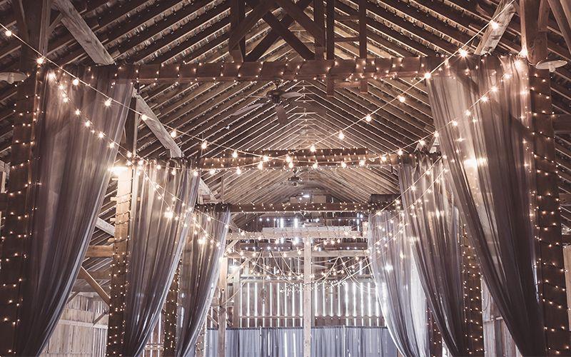 Scheune als Hochzeitslocation dekoriert mit vielen Lichtern