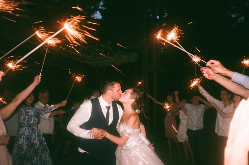 Schönes Brautpaar küsst sich während Gäste große Wunderkerzen halten