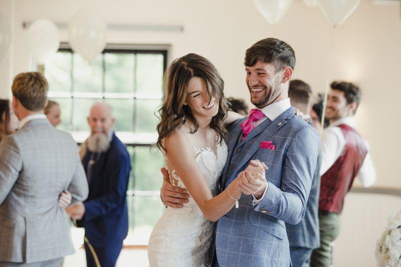 Hochzeitspaar lacht und tanzt in enger Tanzhaltung auf ihrer Hochzeit
