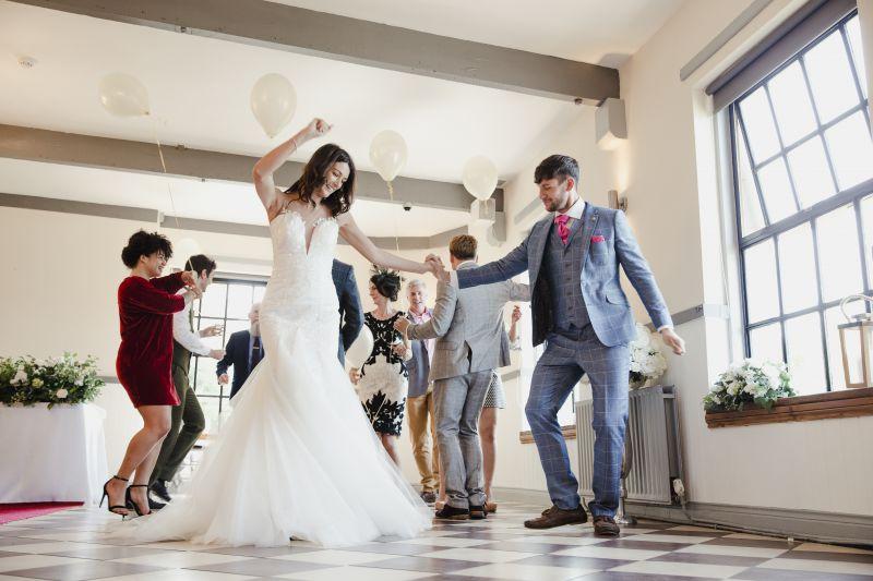 Fröhliches Hochzeitspaar tanzt uf ihrer Hochzeit