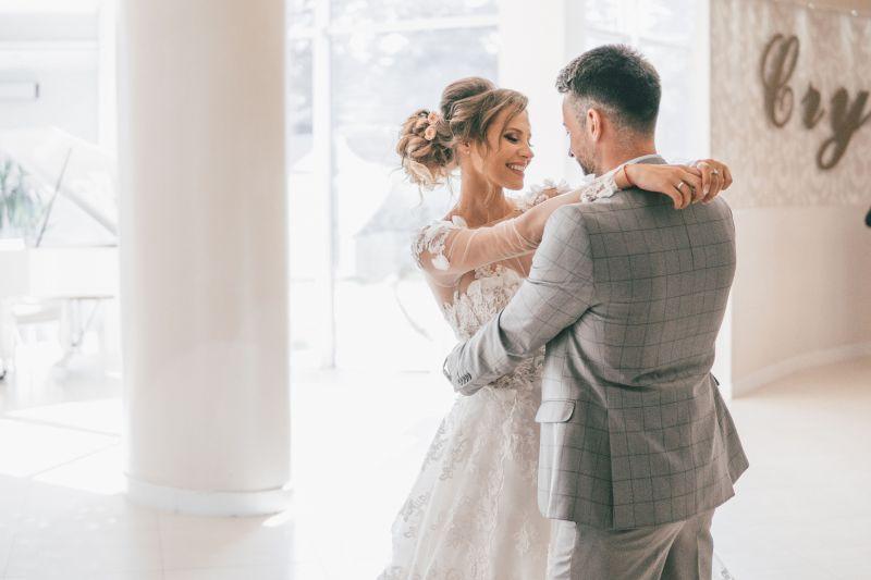 Hochzeitspaar tanzt Eröffnungstanz und schaut glücklich