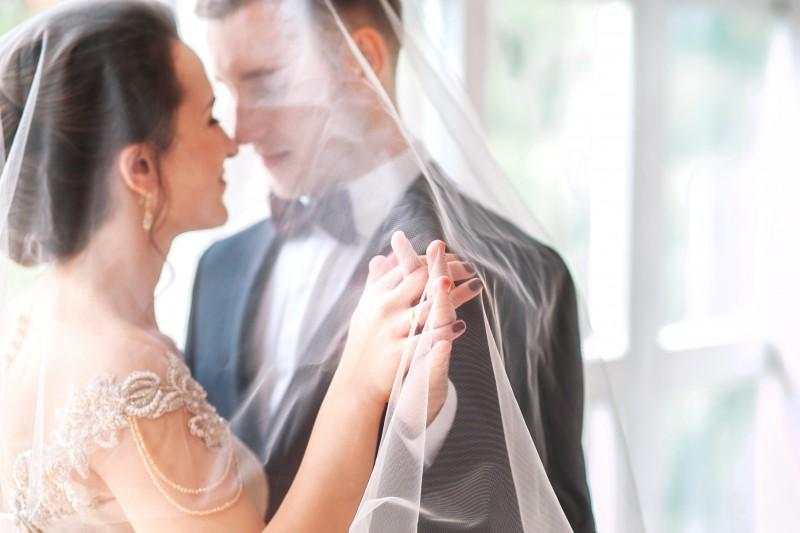 Hochzeitspaar tanzt verliebt unter einem Schleier