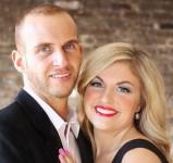 Schön gekleidetes Paar schaut fröhlich in die Kamera