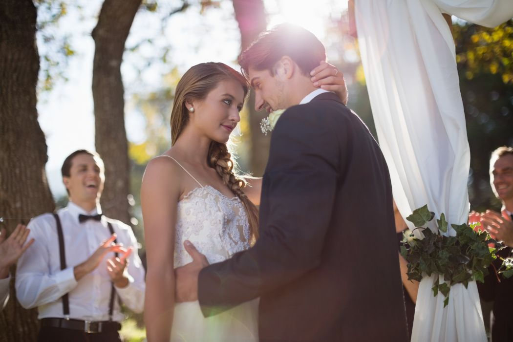 Hochzeitspaar steht in Tanzhaltung vor dem Altar und schaut sich tief in die Augen