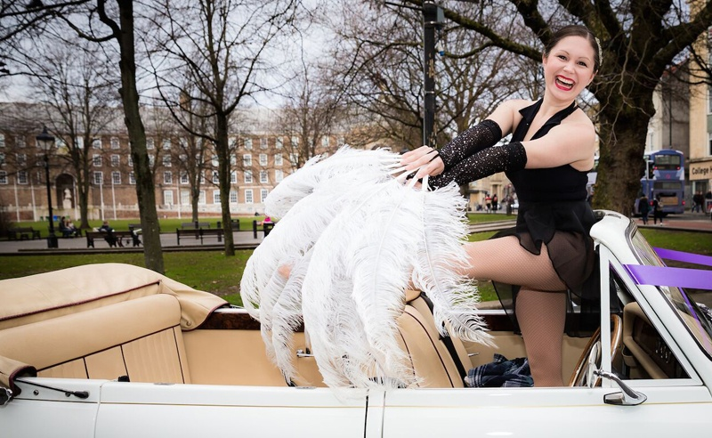 Corporate event entertainment with Amy Young - Image of can can dancer in vintage car in Bristol