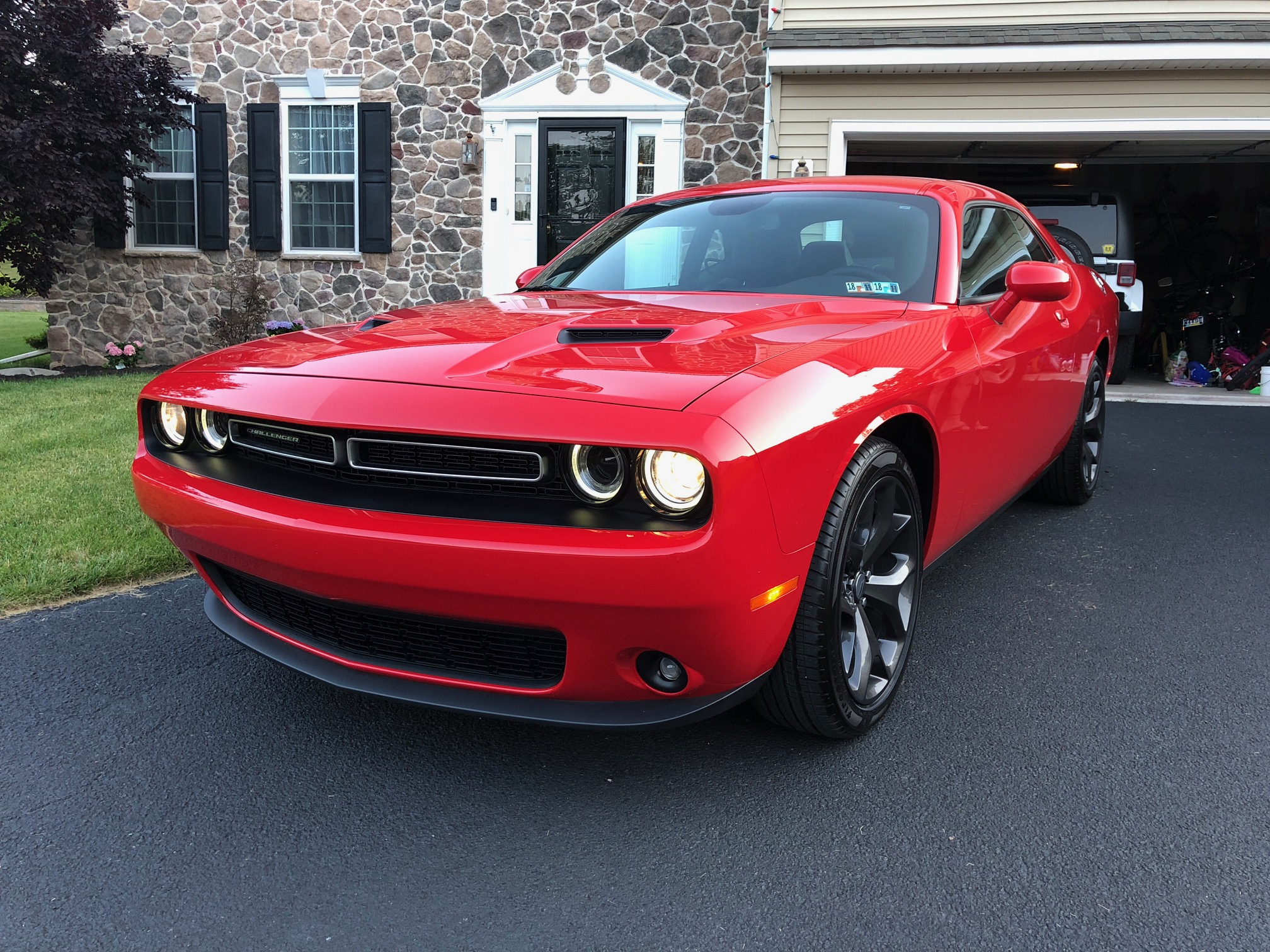 red 2018 dodge challenger parked in the driveway of a suburban home with a stone facade and black shutters