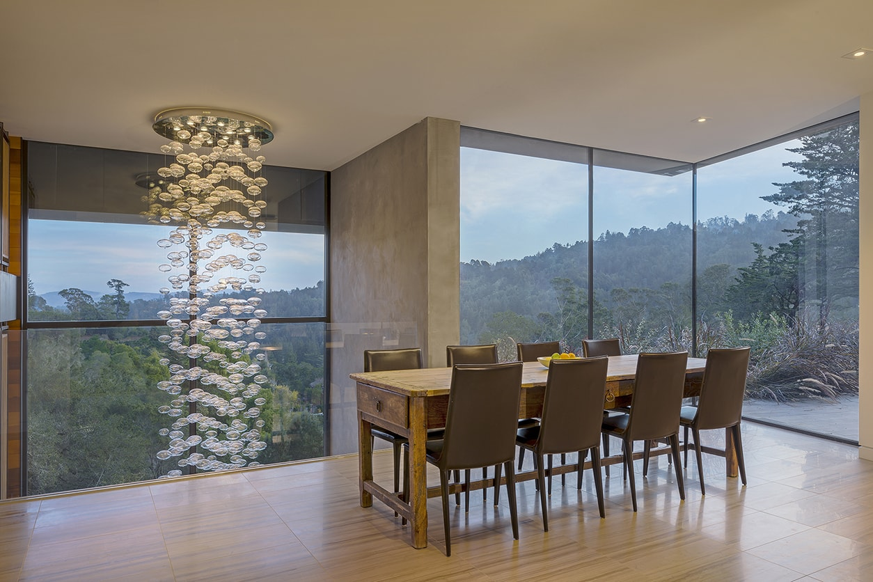 Designed for a tech entrepreneur couple and their young twins, the home in Mill Valley, California is a modern composition in articulated form. Located on a large wooded canyon site and sharing the land with a family of nesting red-tail hawks, this residence is designed to integrate into the landscape through cascading forms and natural materials. The exterior is a montage of natural wood, oxidized steel, and rich zinc panels blending with the surrounding foliage with many of these materials utilized on the interiors as well blurring the lines between inside and out. The main feature of the house is an observatory for the nesting raptors in the tree above visible through the upper level roofs to connect the interior to the beautiful natural surroundings.