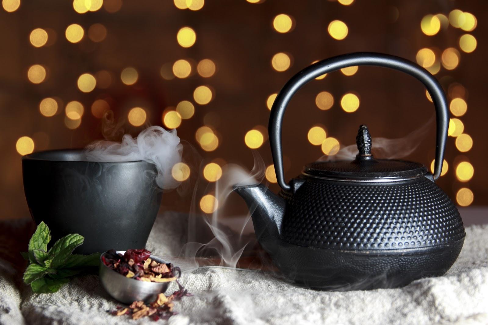 tea cup and kettle black steaming herbal tea