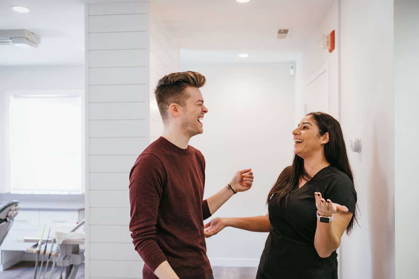 Photo of a female staff member laughing with a male patient.