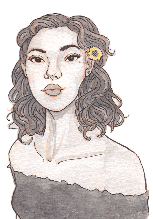 A young model in a frilly shirt with a beauty mark below her left eye and a golden flower in her shoulder-length wavy hair.