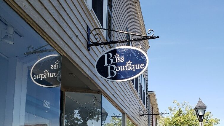 Bliss boutique black and white outdoor blade sign on side of building