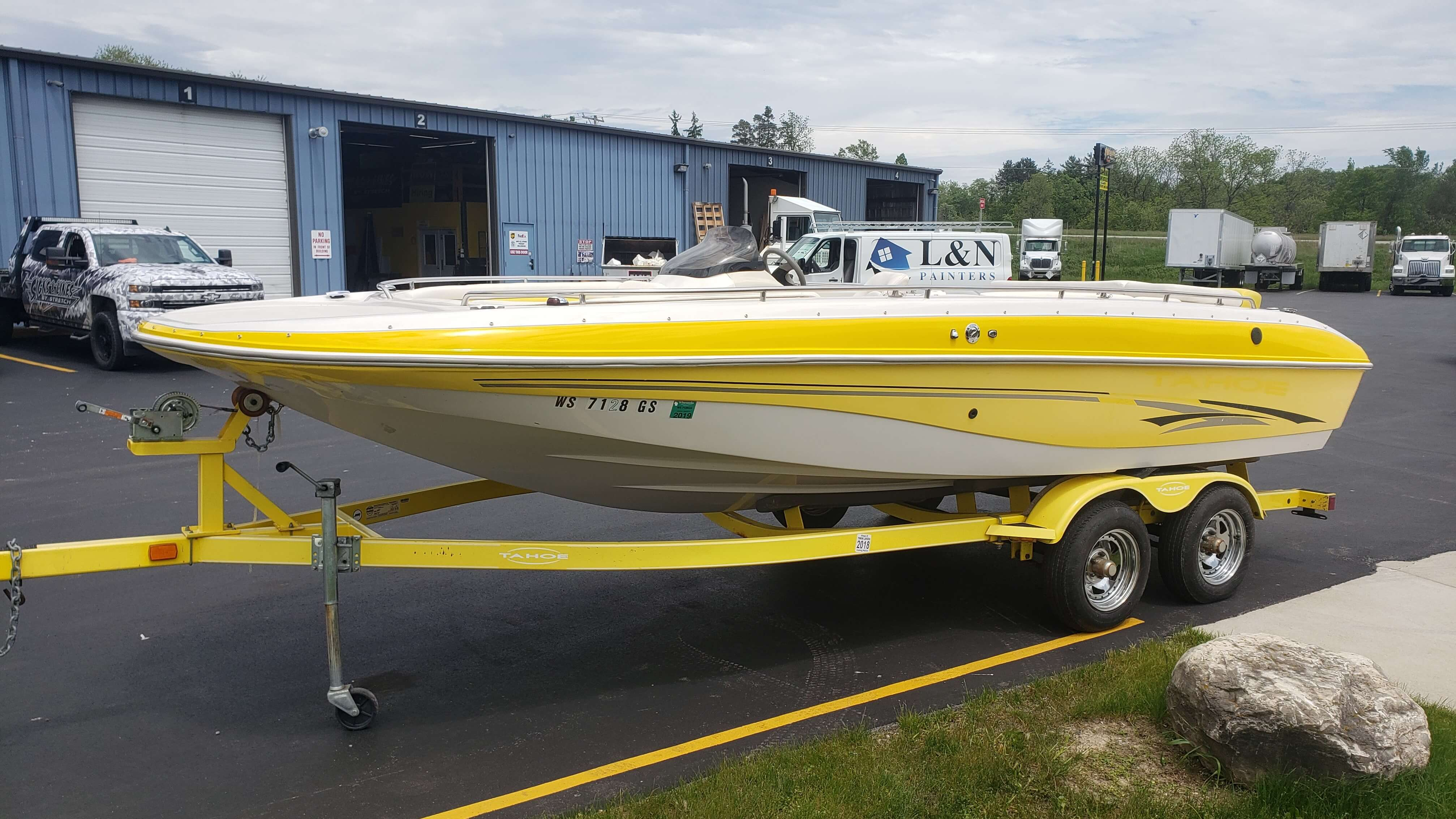 Earth tone pontoon boat vinyl wrap on trailer at Signs and Lines Lot with black and brown striping