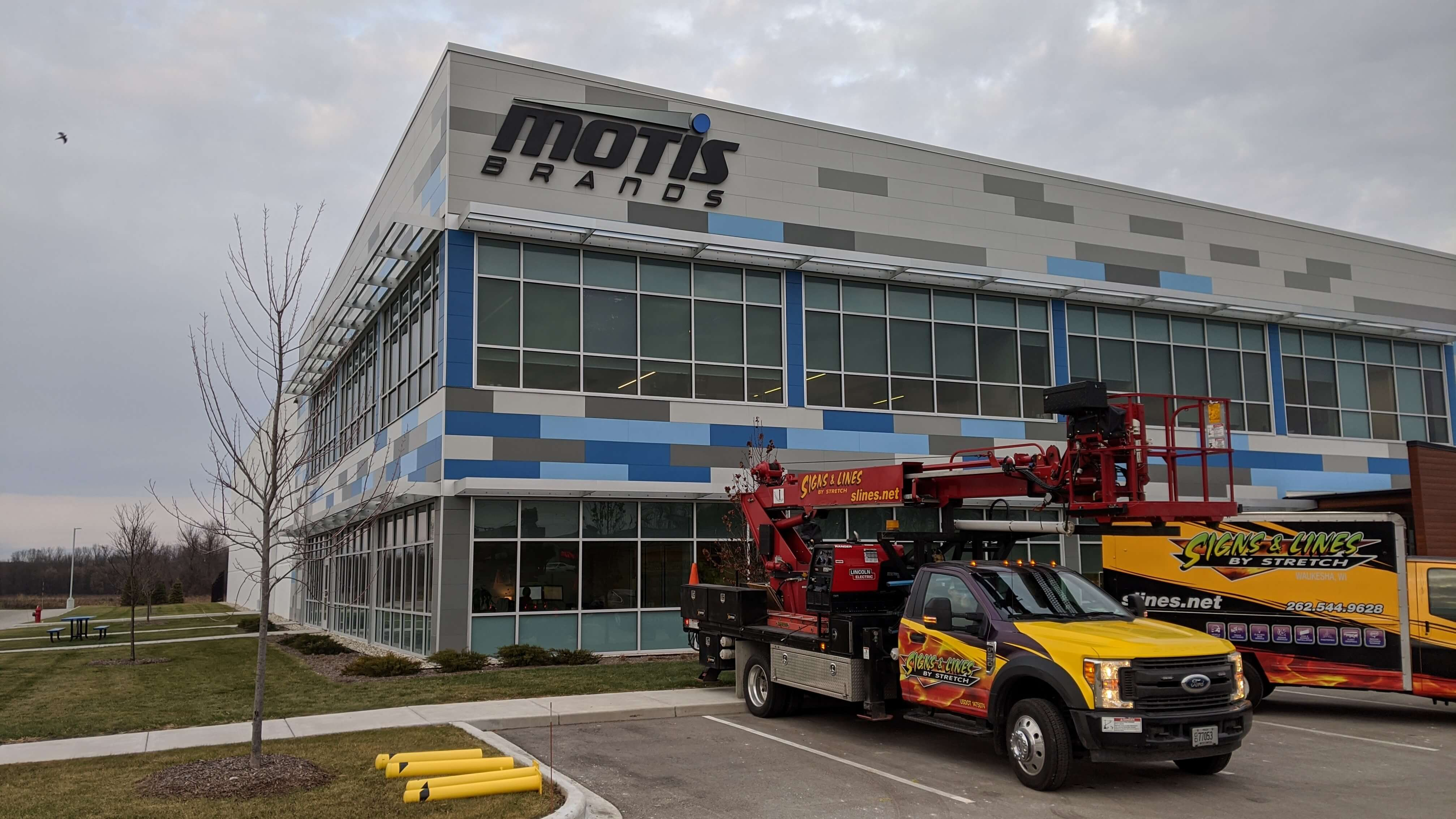Motis Brands Sign Installation by Signs and Lines with Bucket Truck installing the sign