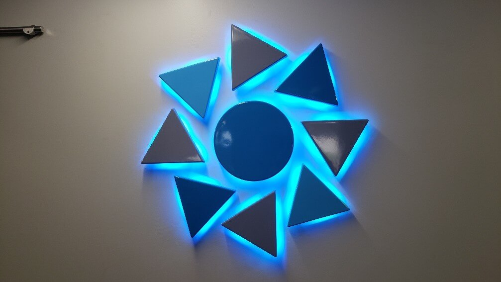 Interior Circular with Triangles Lobby Sign that is Halo Lit in blue, with blue sign faces