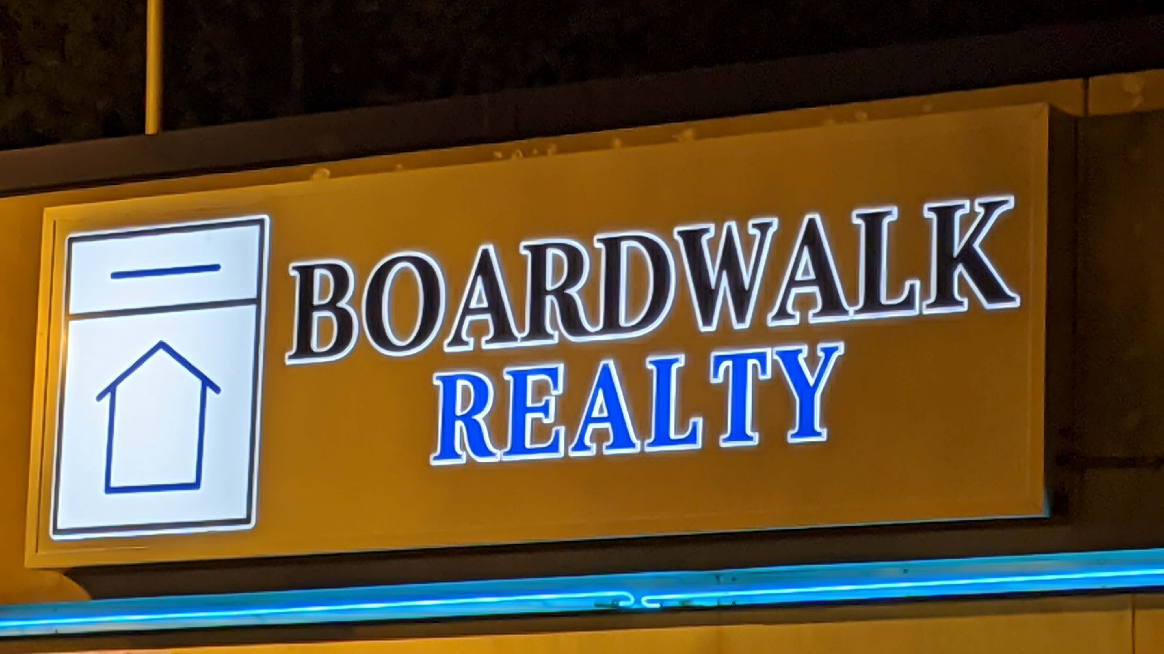 Boarwalk Reality lit sign at night with halo lighting, logo, and different colors