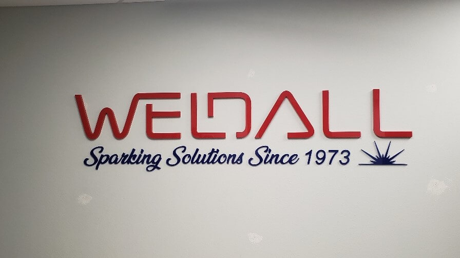 Weldall interior lobby sign with custom font and color scheme produced by Signs and Lines