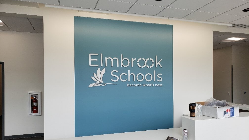 Elmbrook Schools Lobby Sign on Blue Background with White Lettering by Signs and Lines by Stretch