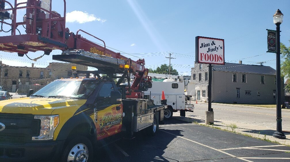 Outdoor pole sign being installed by Signs and Lines with the service truck in the air