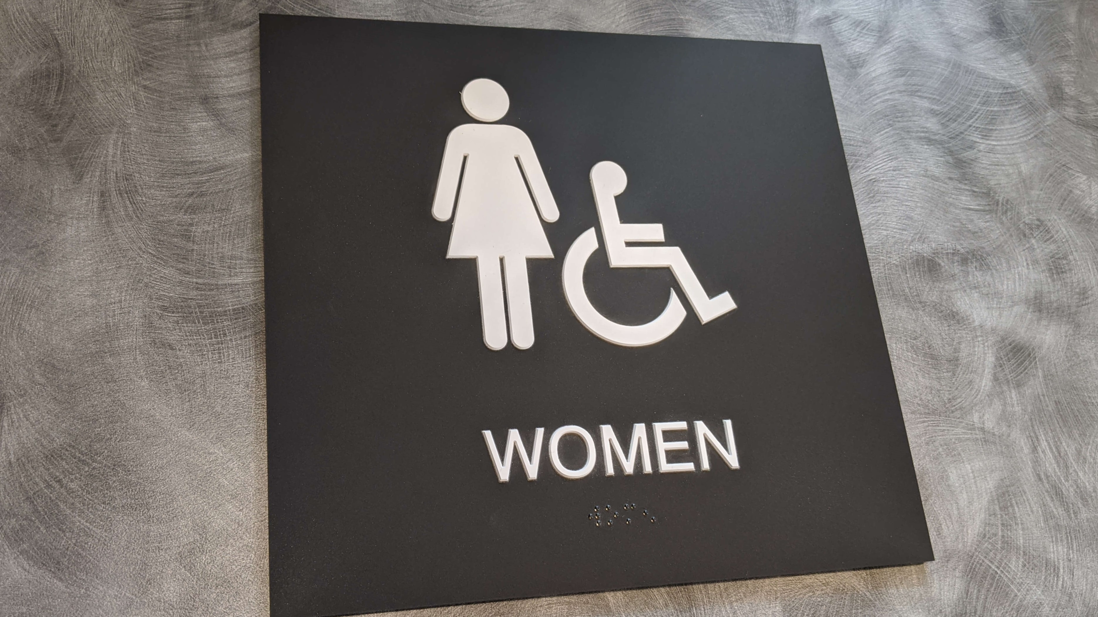 Womens ADA Sign on Grey Wall with white ADA Logo and Woman Logo on the placard