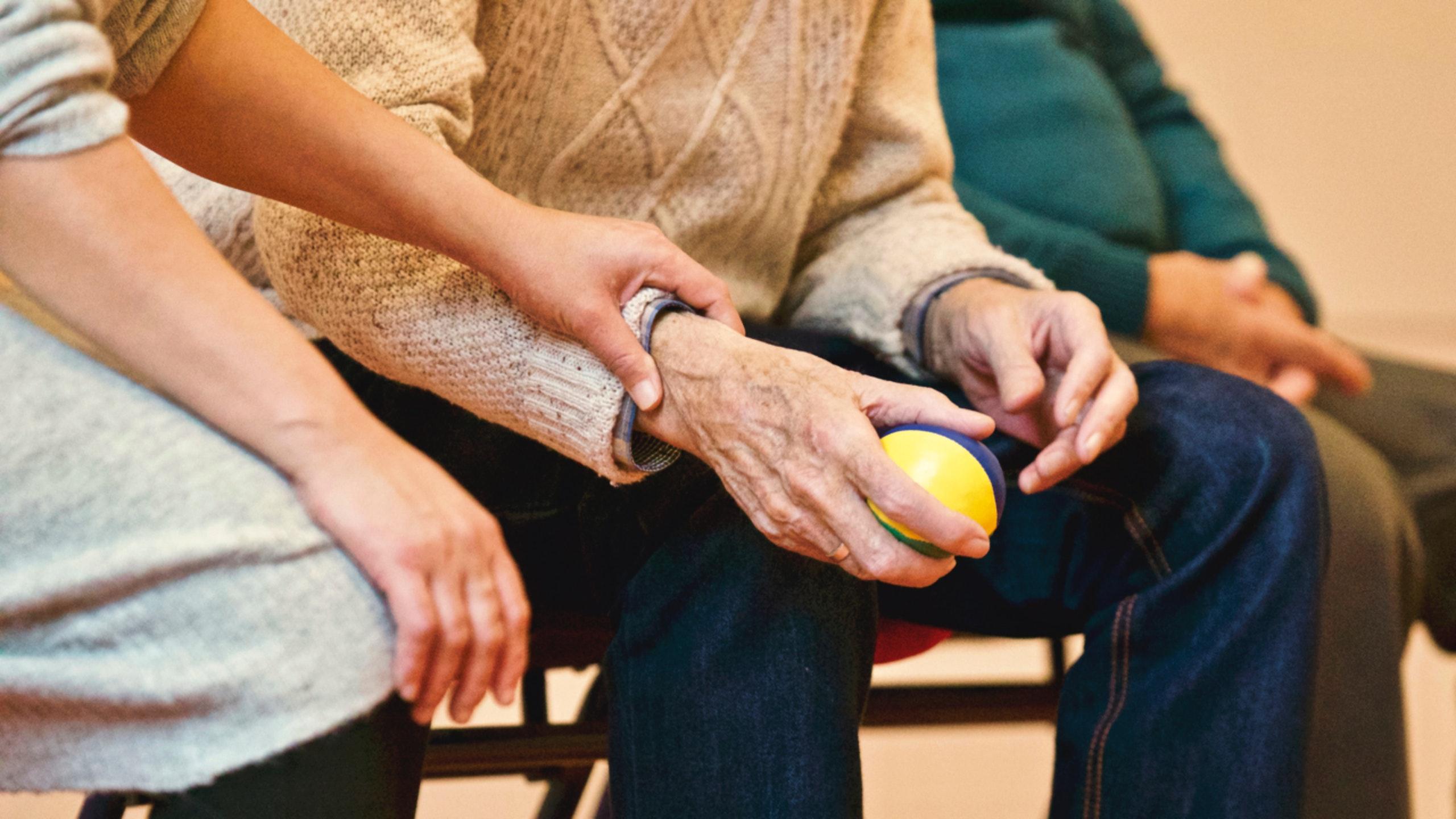 Bild på äldre person som håller en boll