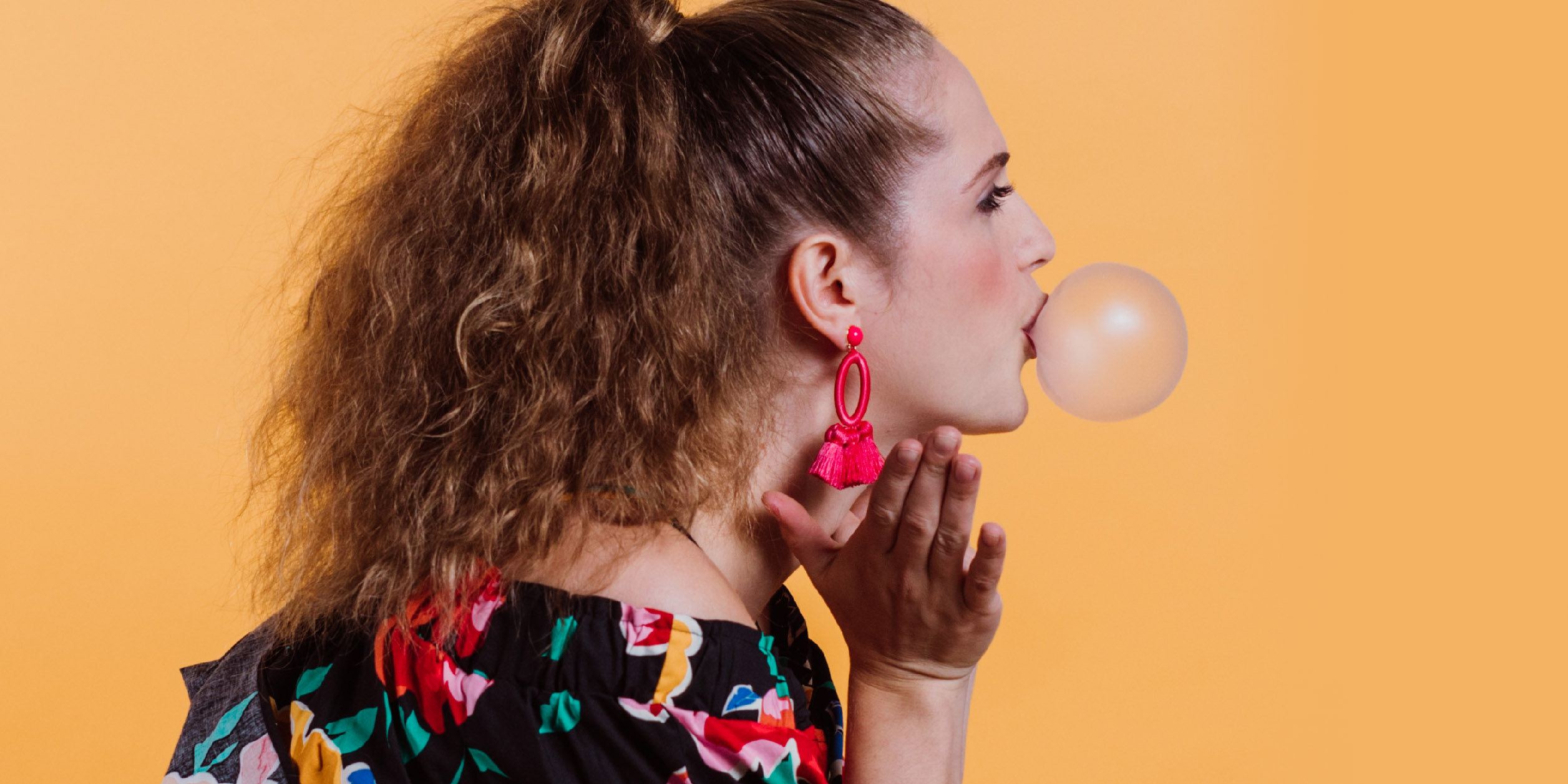 profile of millennial girl in funky clothes blowing a bubble out of gum