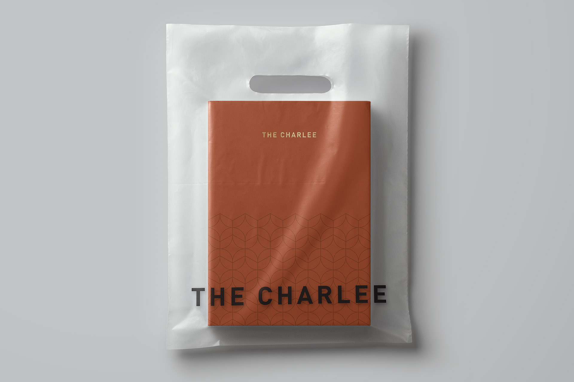 A book inside a transparent bag with The Charlee salon's logo on it