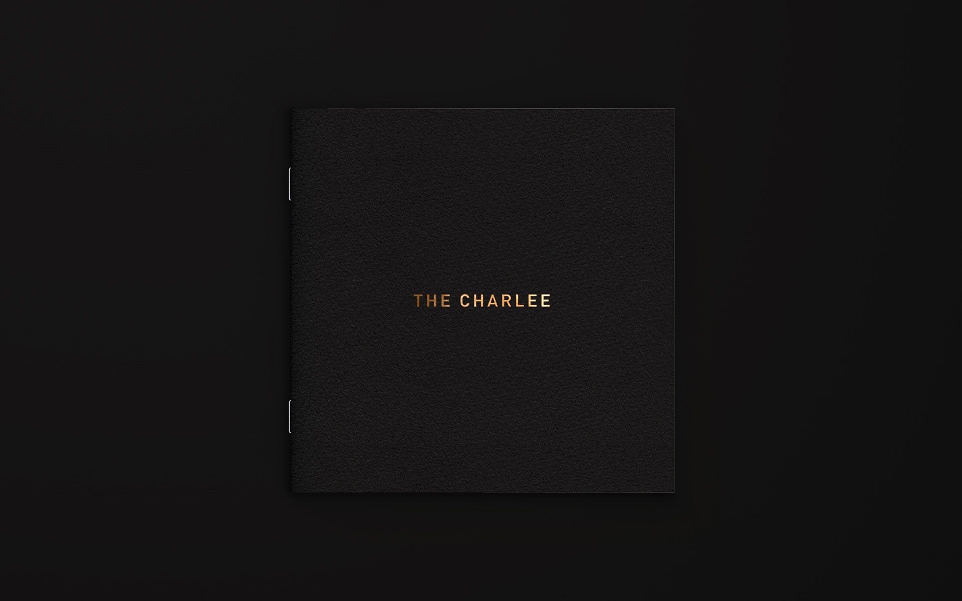 The Charlee salon's brochure cover with gold foil logo