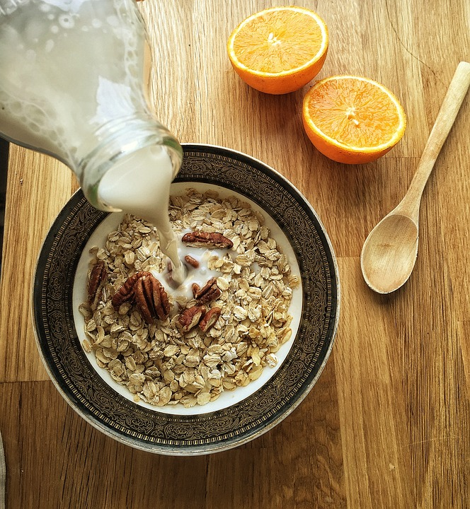 Plant milk is poured from a glass bottle into a bowl, bordered in black with an ornate brown pattern, with oats and walnuts. On the right side are a wooden spoon and an orange cut in half.