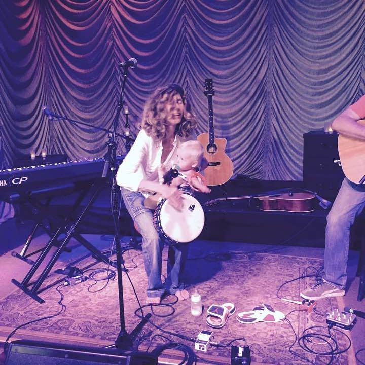 Sophie B Hawkins playing tambourine holding her infant daughter