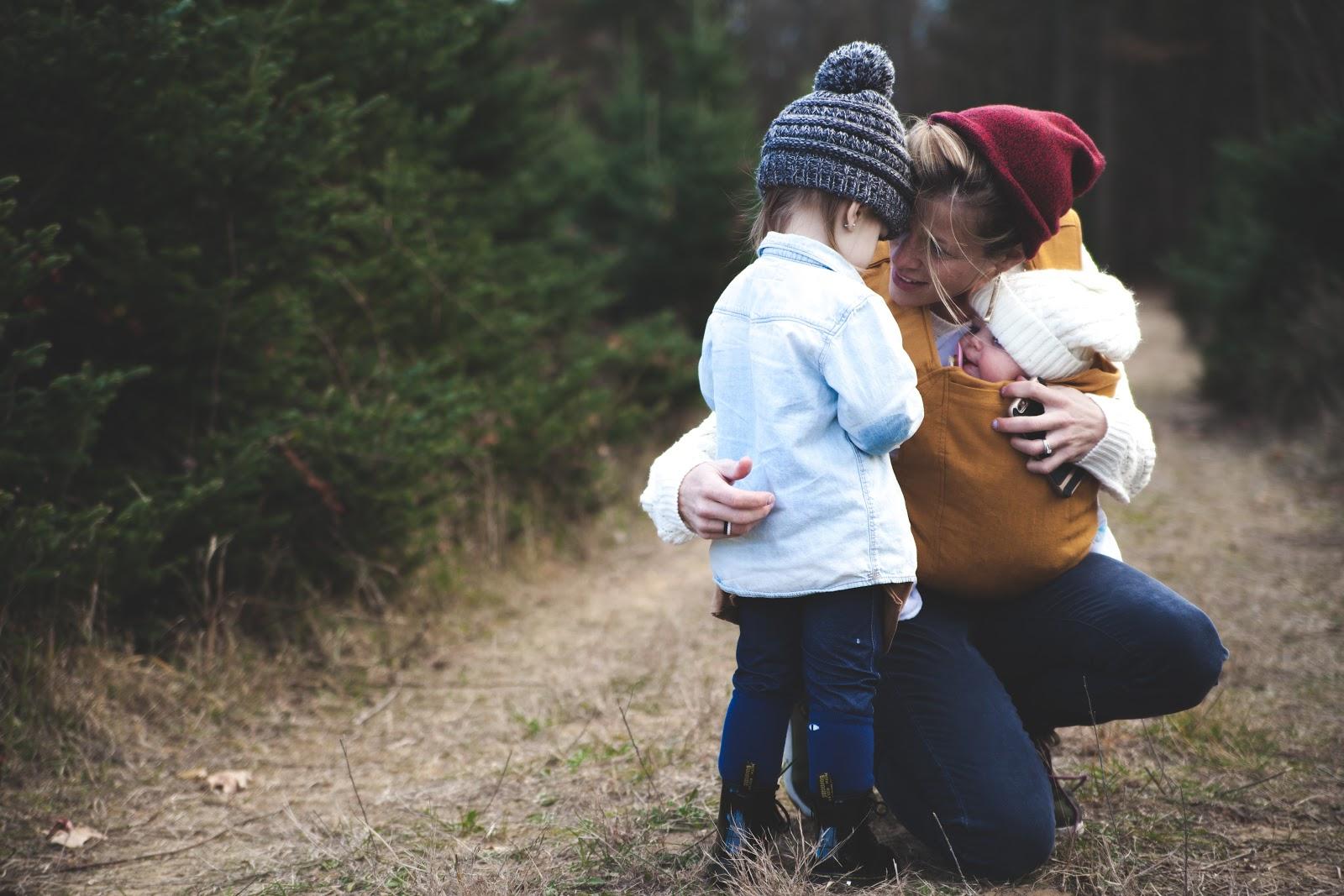 Mother holding infant and hugging toddler