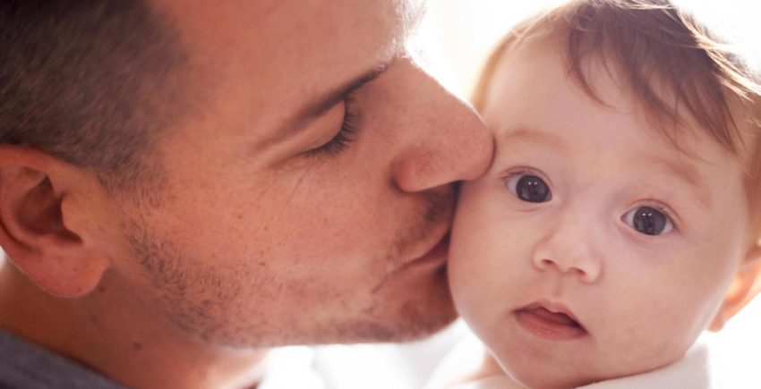 A father kisses his baby on the cheek