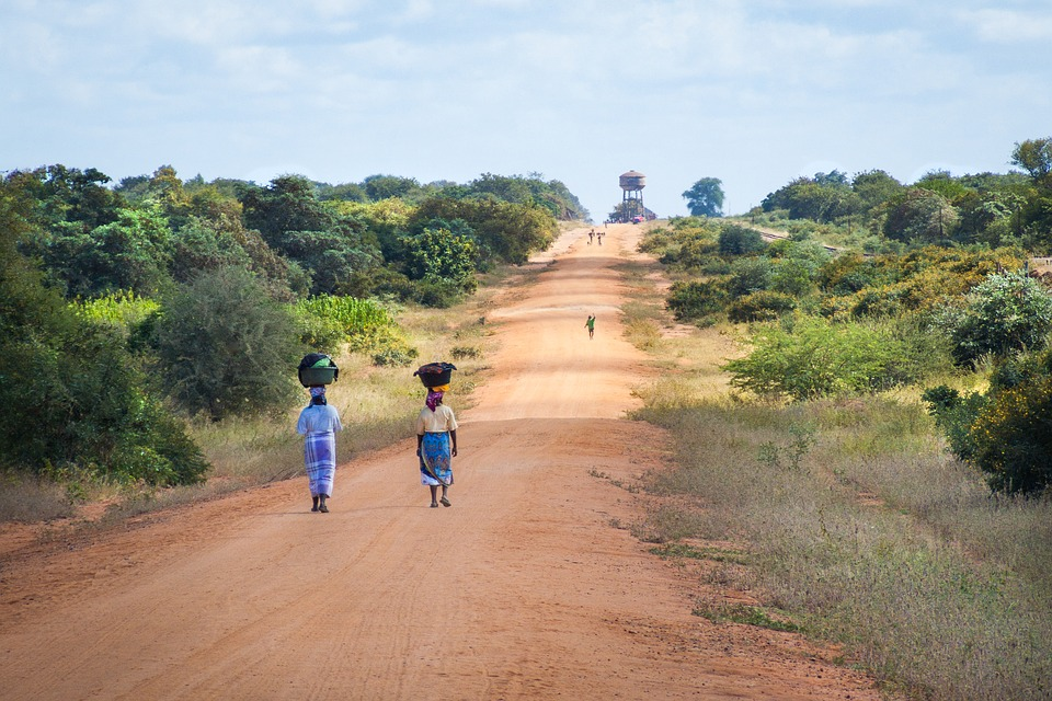 Two African women walk down the road carrying baskets on their heads.