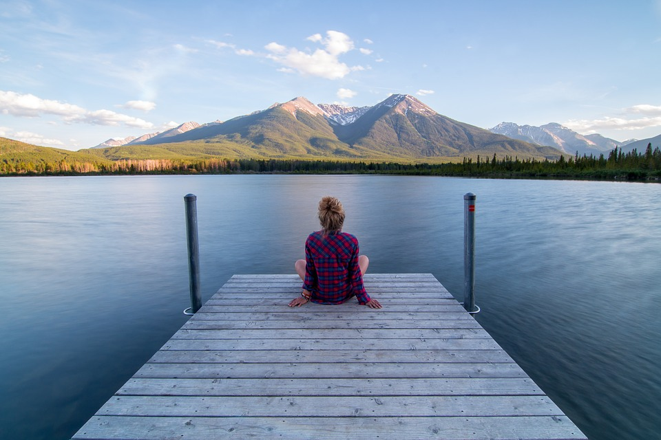 Young mother relaxes in a serene lake setting with mountains in the distance