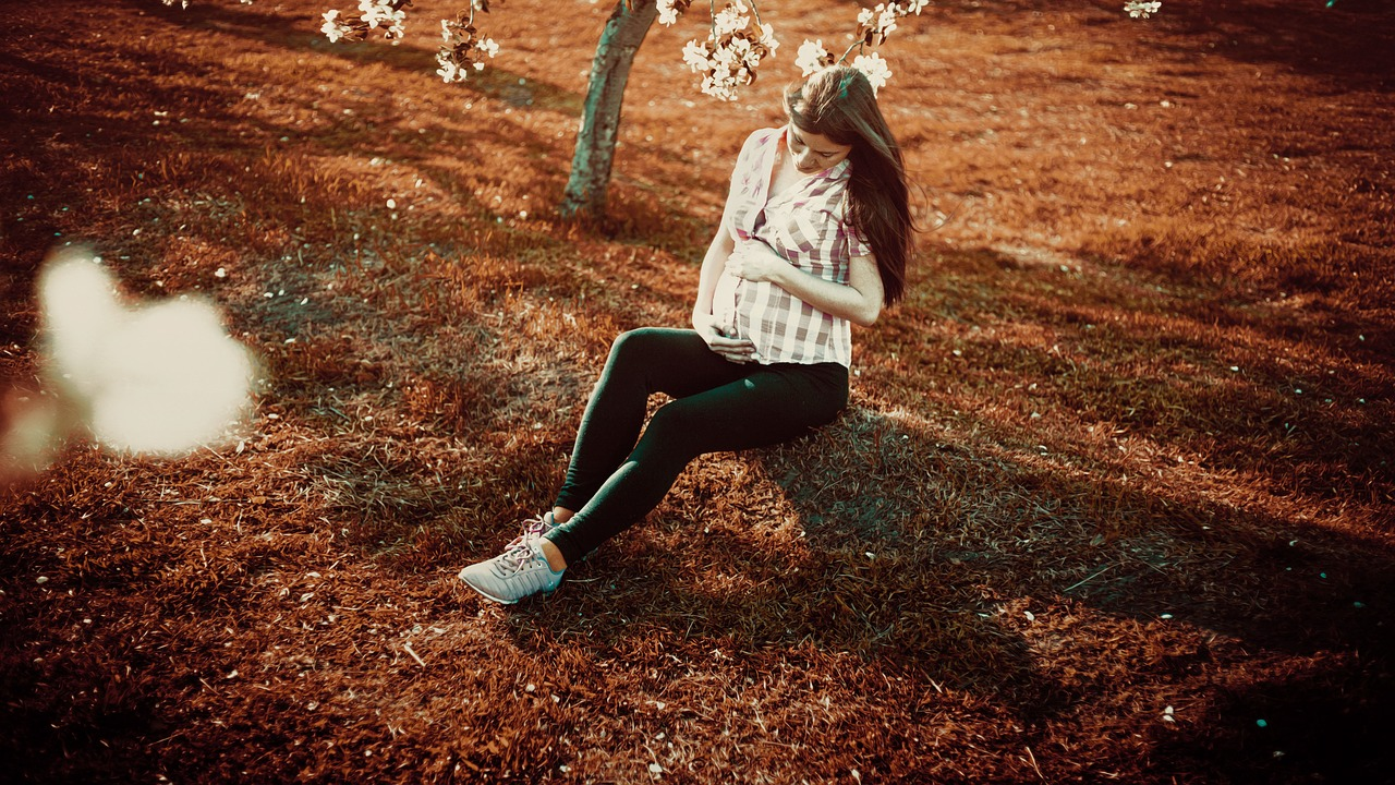 A pregnant woman with PCOS wearing a plaid shirt and leggings sits under a flowering tree on burnt orange grass.
