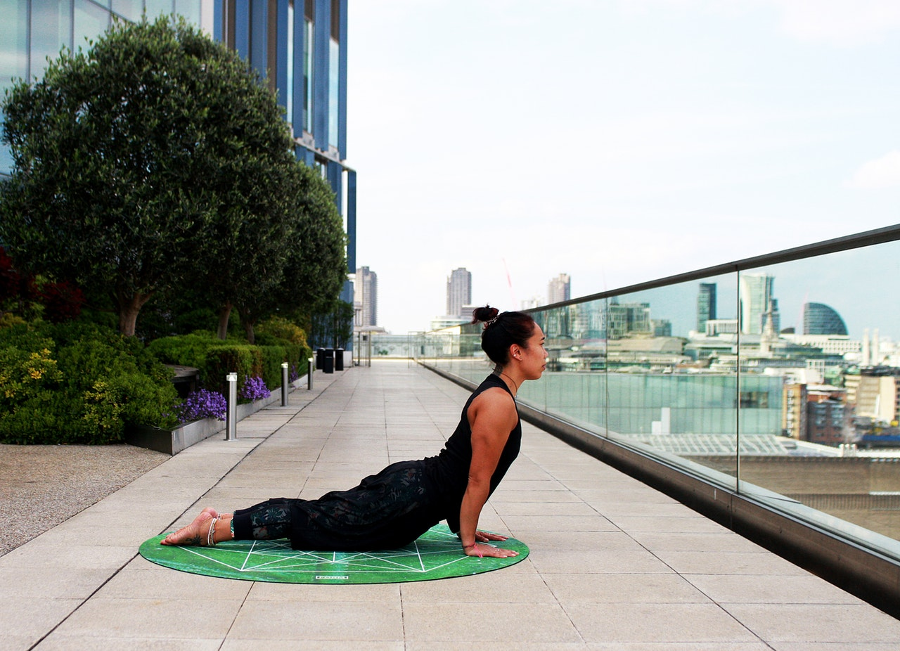 A woman performing a cobra pose on a city balcony. Woman's arms push her body up and curves her back.