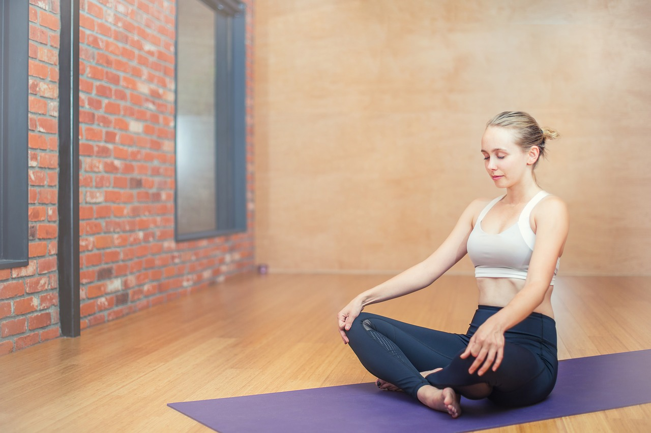 A woman sitting on a yoga mat, her legs crossed and hands resting on her knees. Her eyes are closed.