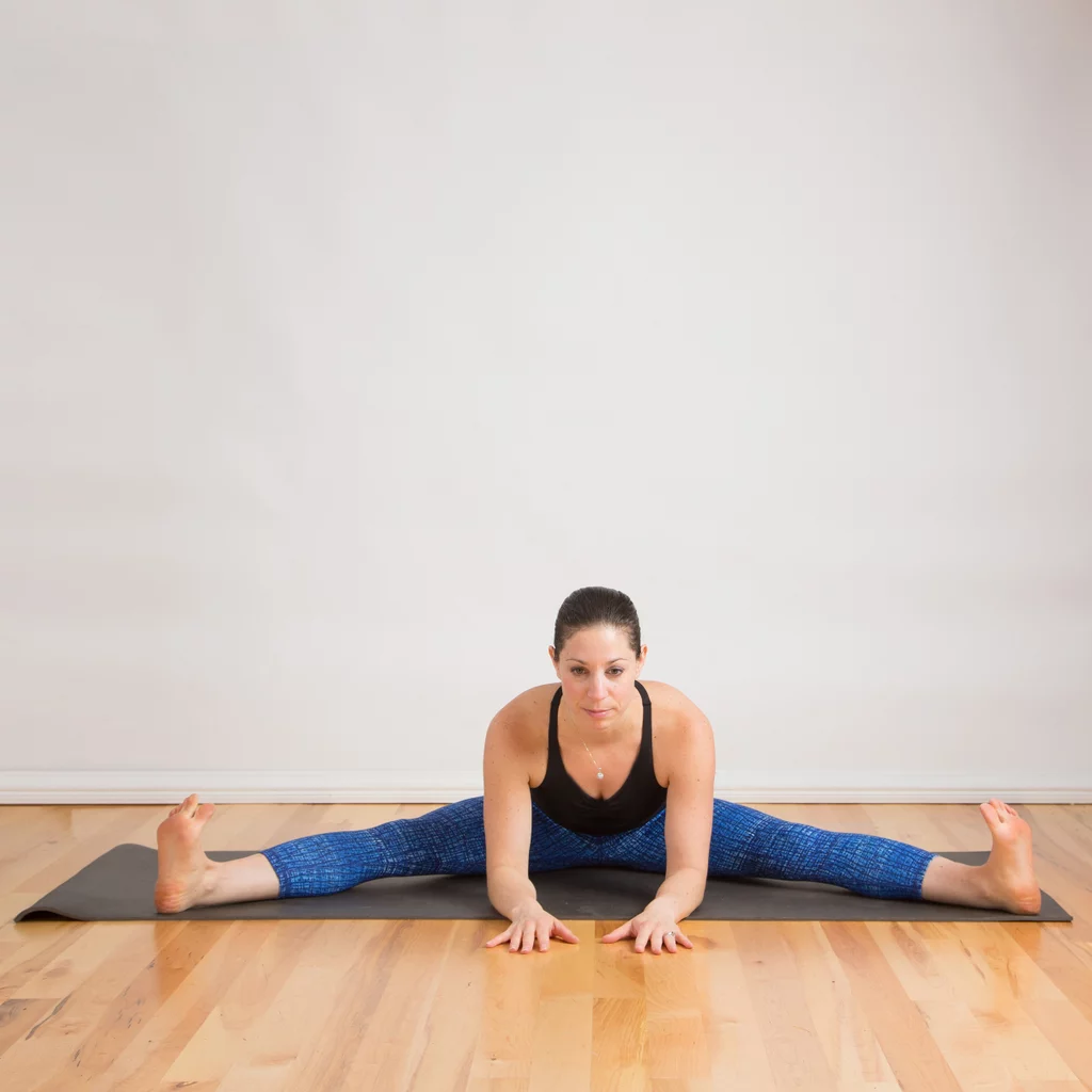 Woman performs the forward-bend straddle stretch