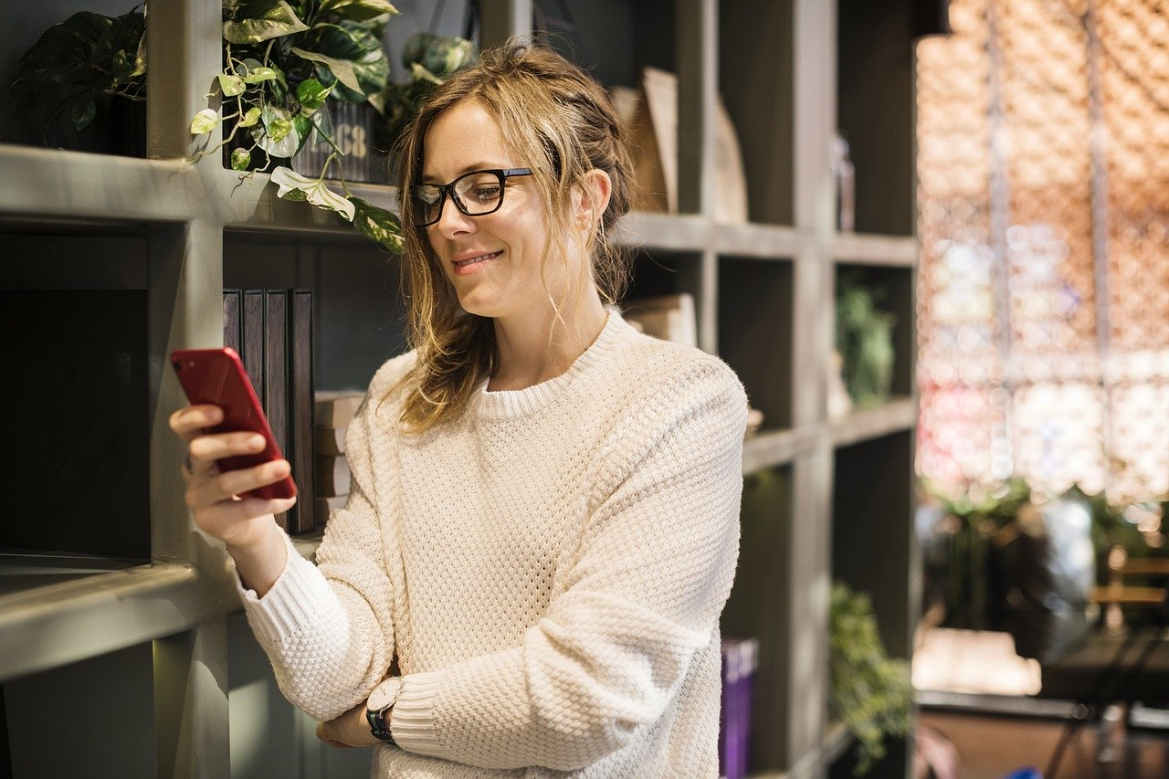 A woman standing by a bookcase, smiling as she looks at her phone.