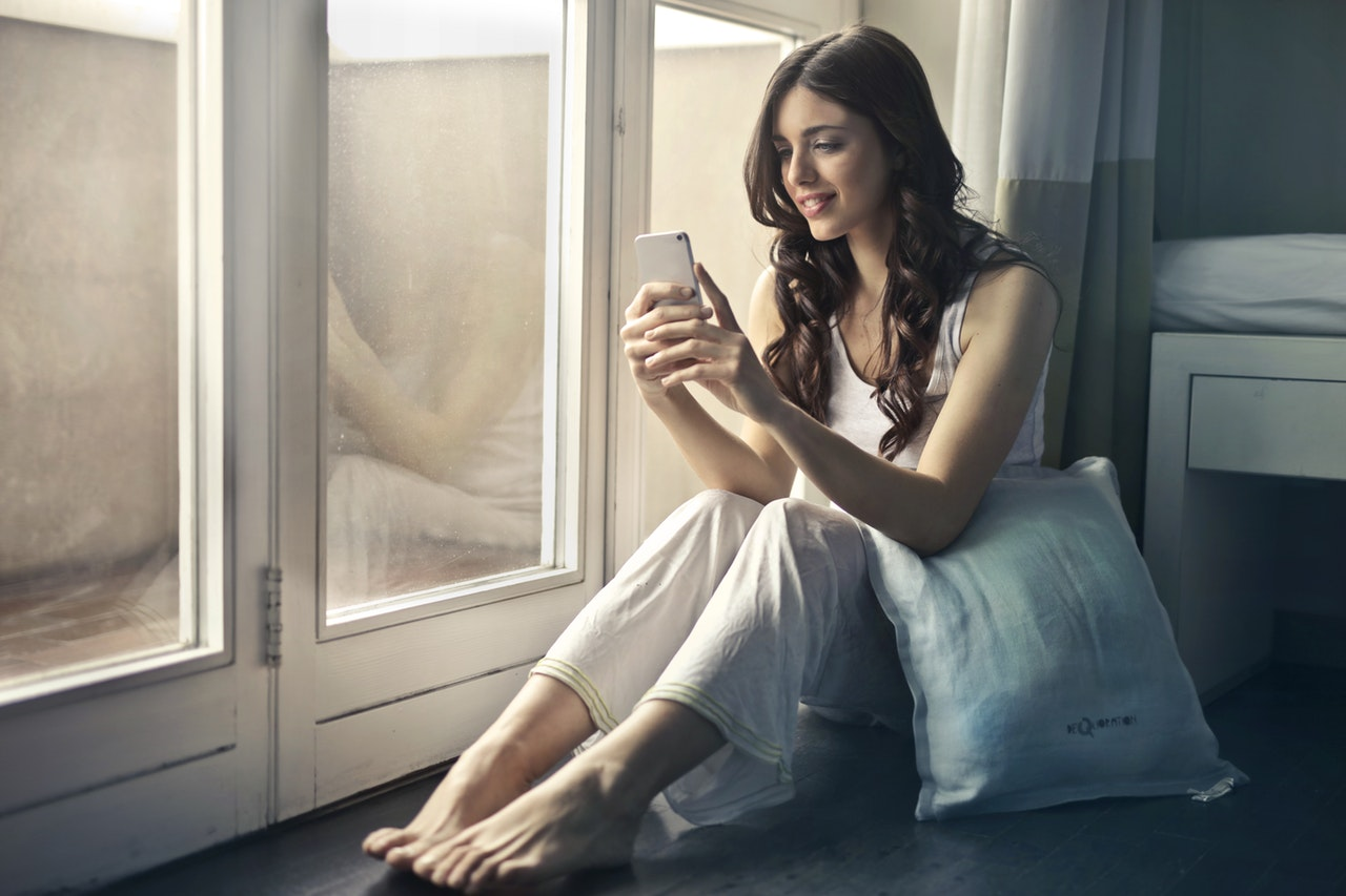 Woman sitting by window looking at her phone