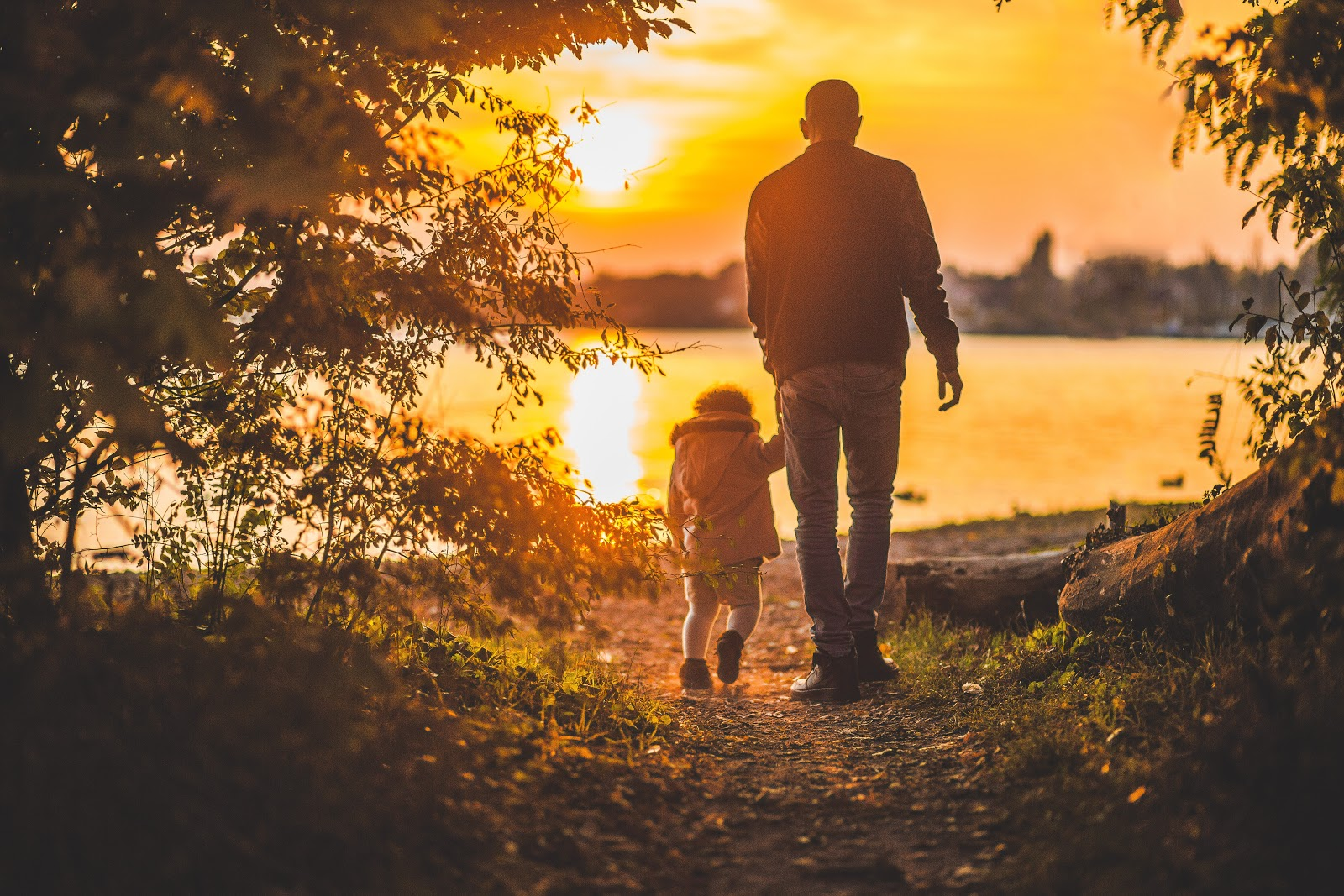 father and child walking during sunset
