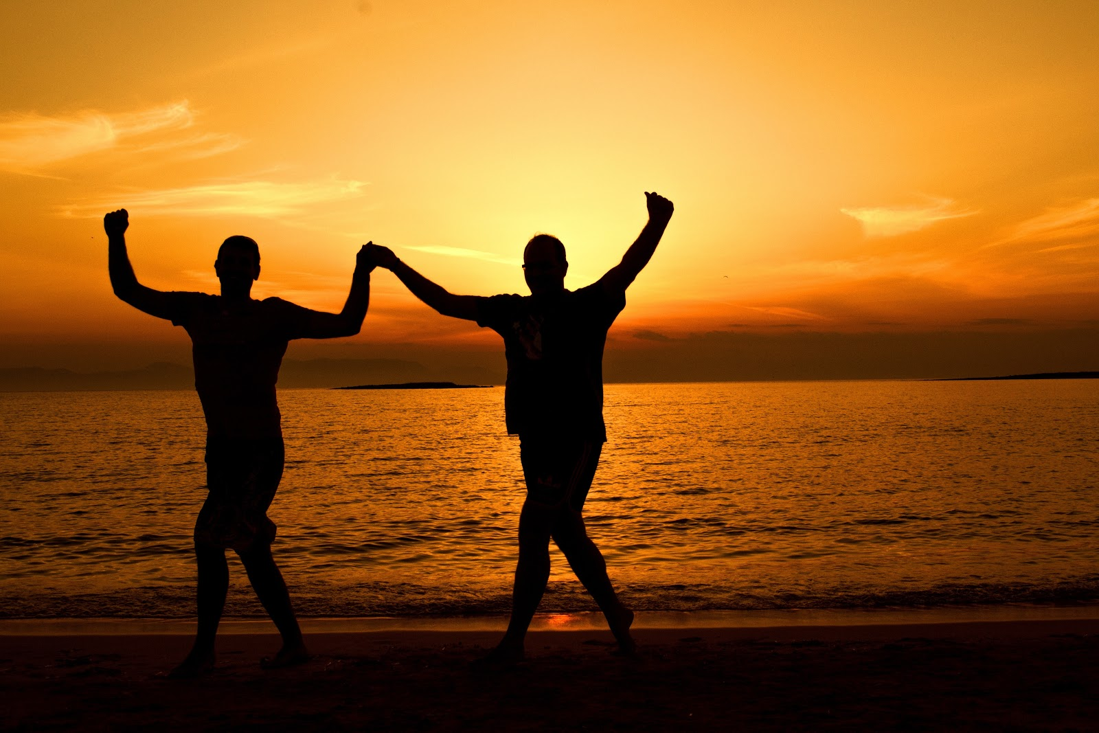 Silhouette of couple holding hand up in celebration agaisnt an ocean and sunset