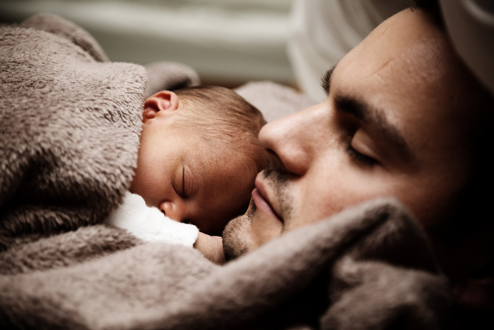 A father takes a nap with his child sleeping on his chest.